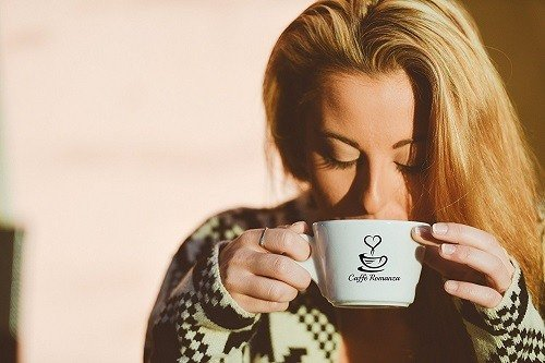 Woman Drinking Coffee from Caffee Romanza Cup