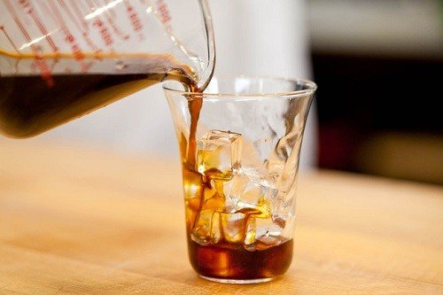 Pouring Cold Brew Iced Coffee into a Glass filled with Ice