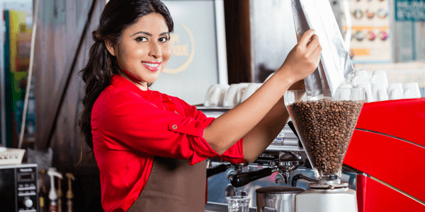 Woman Grinding Beans In Burr Coffee Grinder
