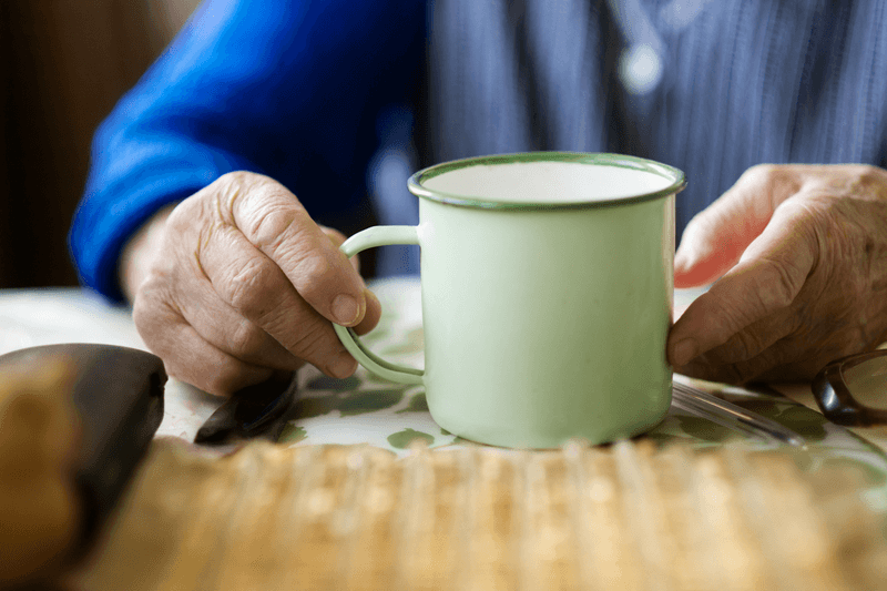 Elderly Person With A Cup Of Low Acid Coffee