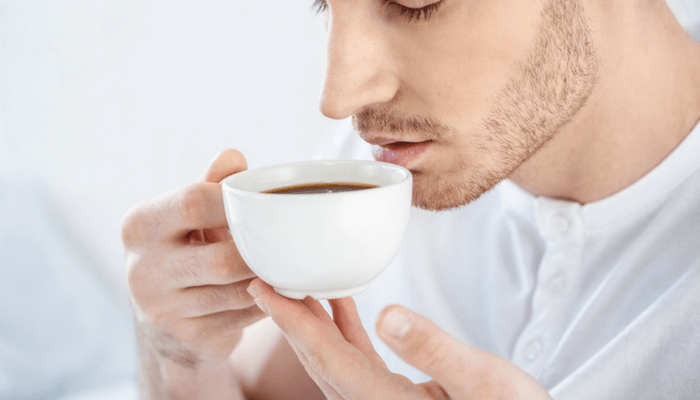 Young Man Drinking Coffee Before Bed