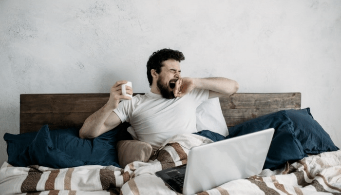 Gentleman Laying In Bed Yawning And Drinking Coffee