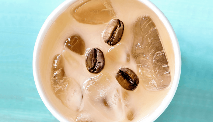 Frappe With Coffee Beans Floating In It On A Blue Background