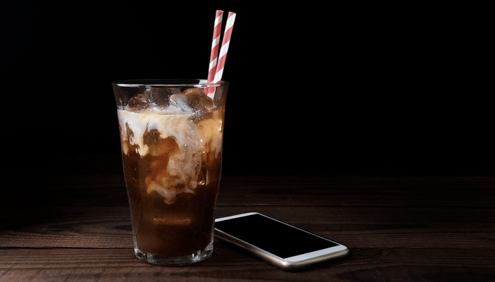 Iced Coffee With A Cell Phone On Dark Background