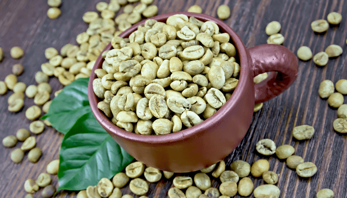 Non Roasted Coffee Beans In A Brown Mug On Wooden Background