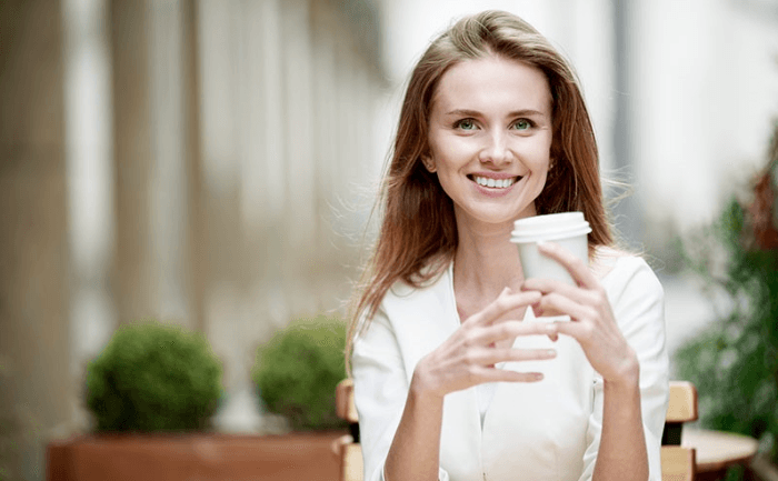 Young Woman Drinking A Cup Of Nitro Coffee