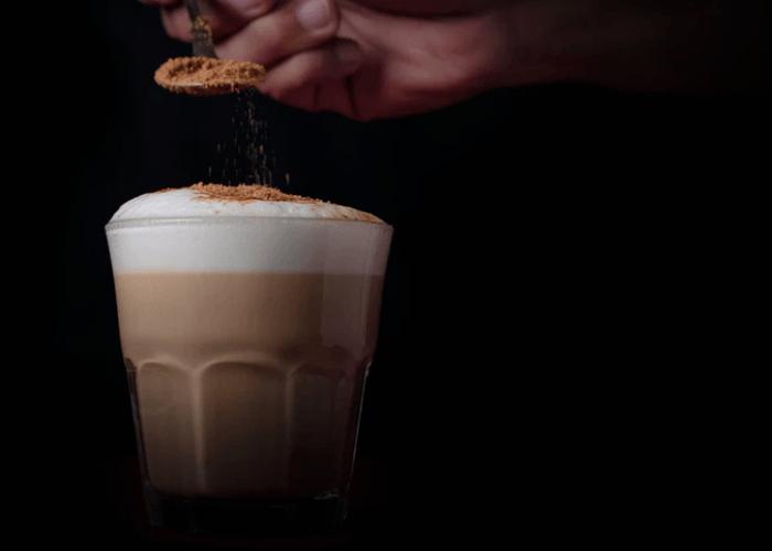 A Glass Of Espresso Topped With Crema On Black Background