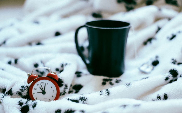 Coffee Cup And Alarm Clock On A Blanket