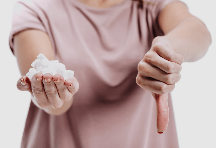 Cropped closeup of woman holding unhealthy white sugar with thumb down