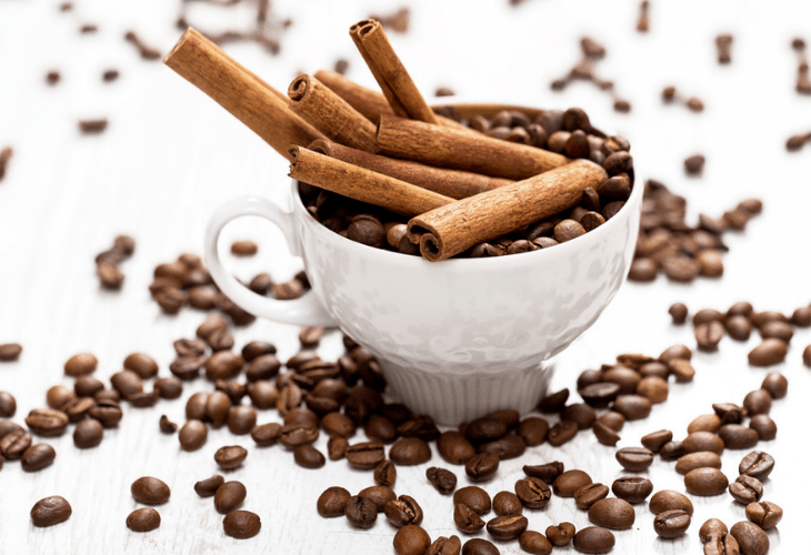 Cinnamon sticks and coffee beans in a white cup