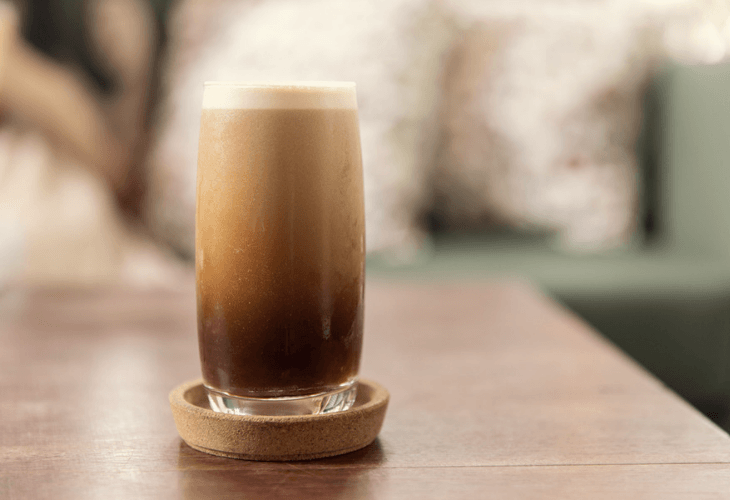 Nitro coffee drink in a glass foaming with bubbles