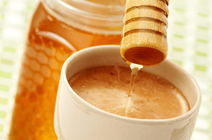 Adding honey to a cup of coffee