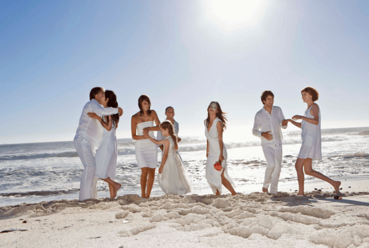 The wedding party having fun on the beach at destination wedding