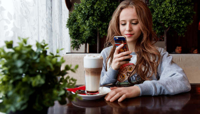 Young woman enjoying a beverage at her local coffee house
