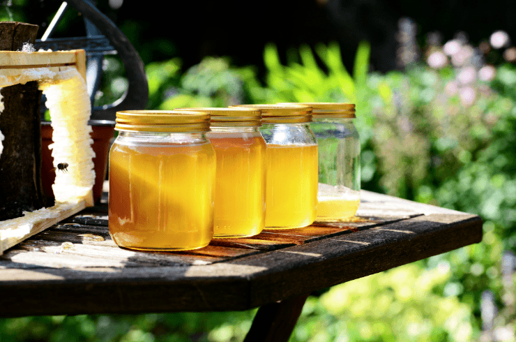 Honey jars on a table near a beehive in the garden