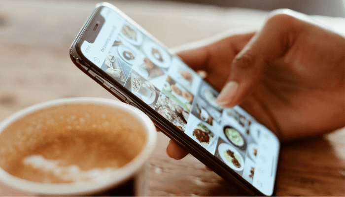 Hand with iPhone ordering in coffee shop
