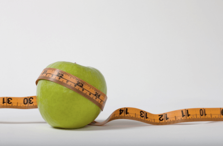 An apple and tape measure, illustrating that skin health and coffee