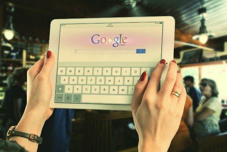 A pair of hands holding up a keyboard open to google