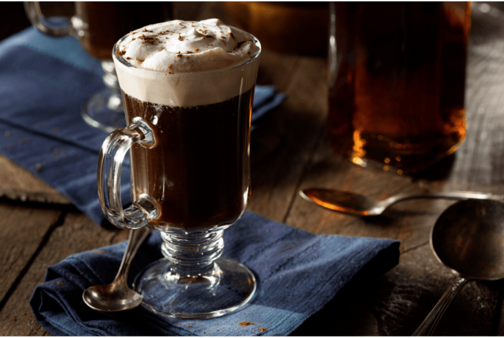 Irish coffee on a blue napkin with a bottle of whiskey