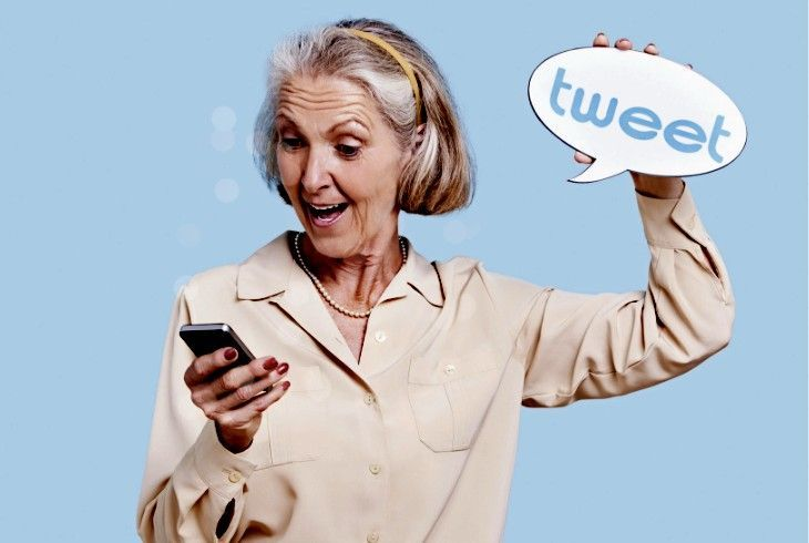 Woman tweeting on her phone holding a sign that says tweet