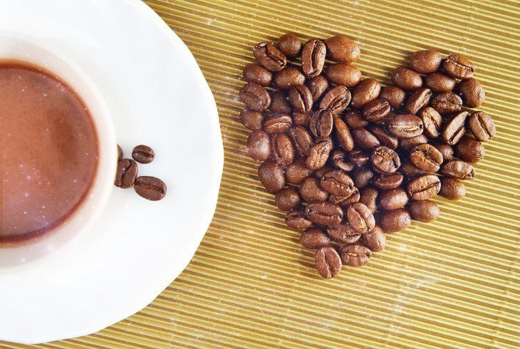 Coffee bean heart next to a cup illustrating the health benefits of coffee