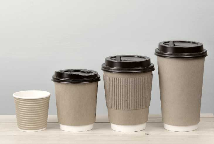 Four paper coffee cups with blue background
