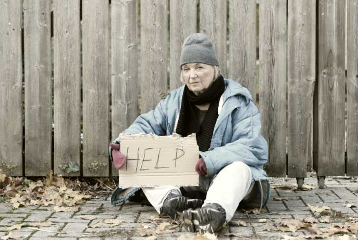 Homeless woman holding a help sign