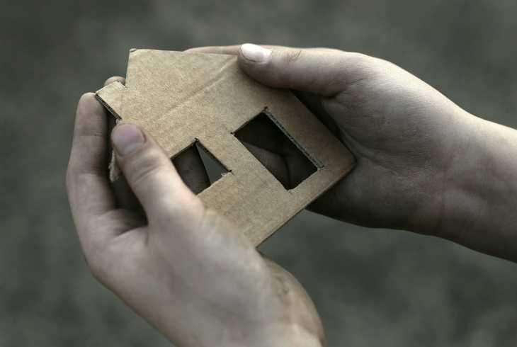 Pair of hands holding a cardboard house outline