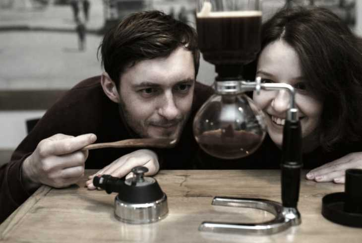 Young couple watching a siphon coffee maker work