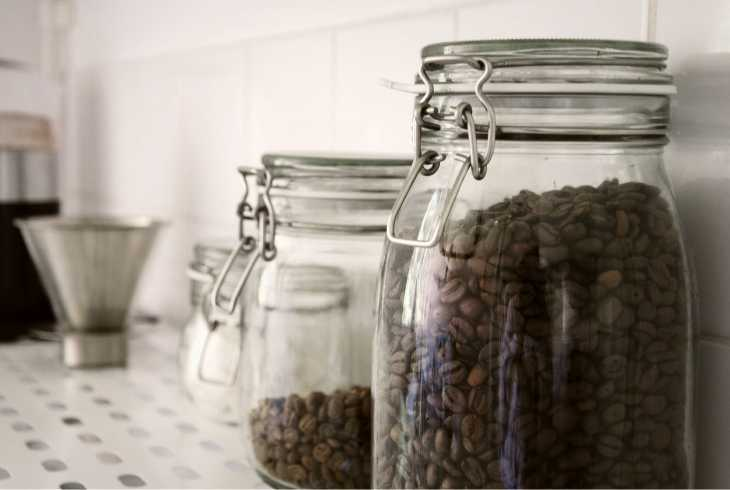 Two airtight jars with coffee beans on a counter