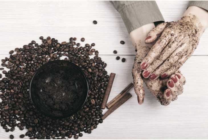 A pair of woman's hands using used coffee grounds to eliminate a strong odor