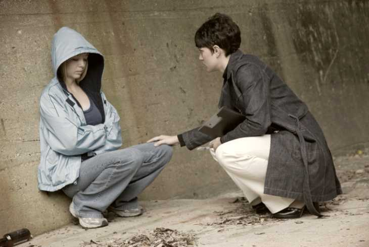 Homeless teenager talking to a woman trying to help