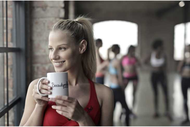 Young woman drinking coffee before workout