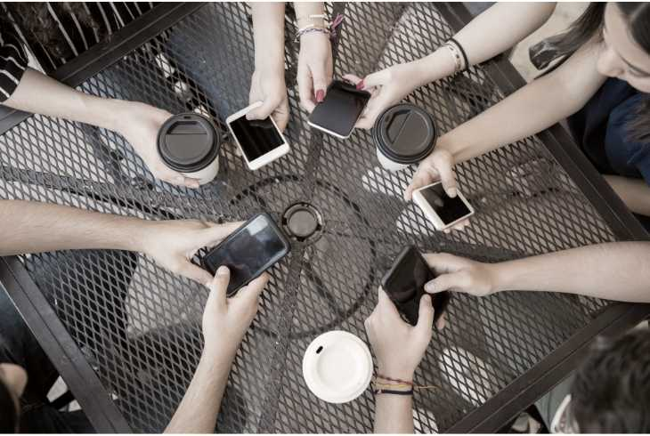 Friends at coffee shop checking social media on their phones