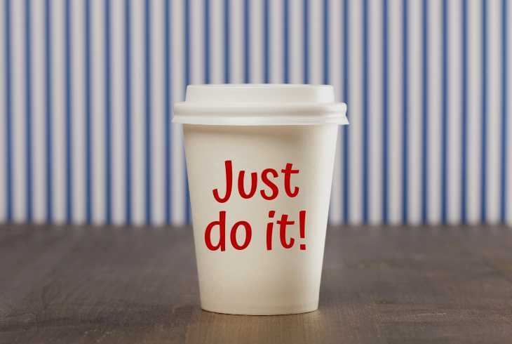 """Just dot it"" on a coffee cup sitting on a table"