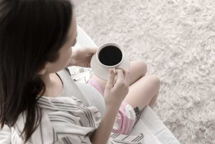 Pregnant woman sitting on the edge of bed drinking coffee
