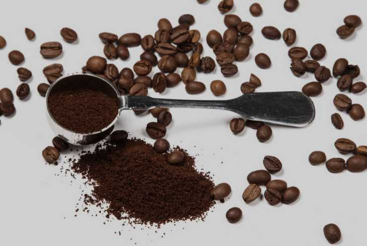 Coffee scoop, beans, ground coffee on a grey background