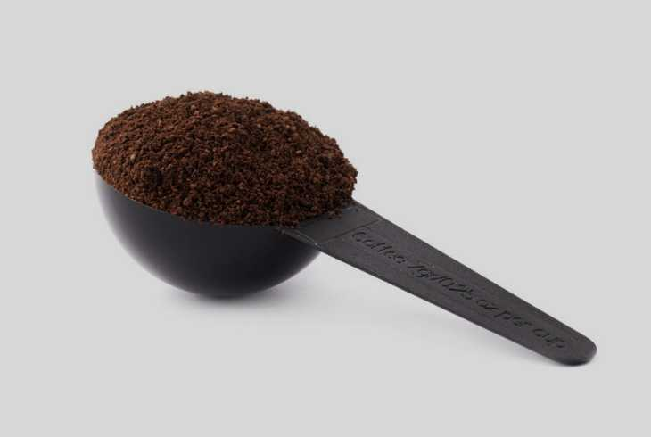 Standard coffee scoop filled with ground coffee on grey background