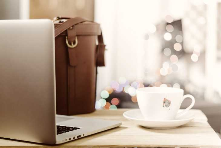 Laptop, briefcase and favorite coffee cup on employee desk