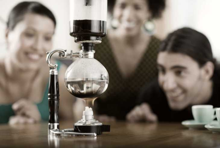 Three friends watching a vacuum coffee maker