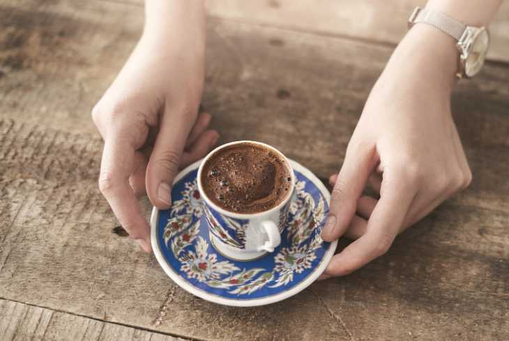 Pair of hands serving Turkish coffee